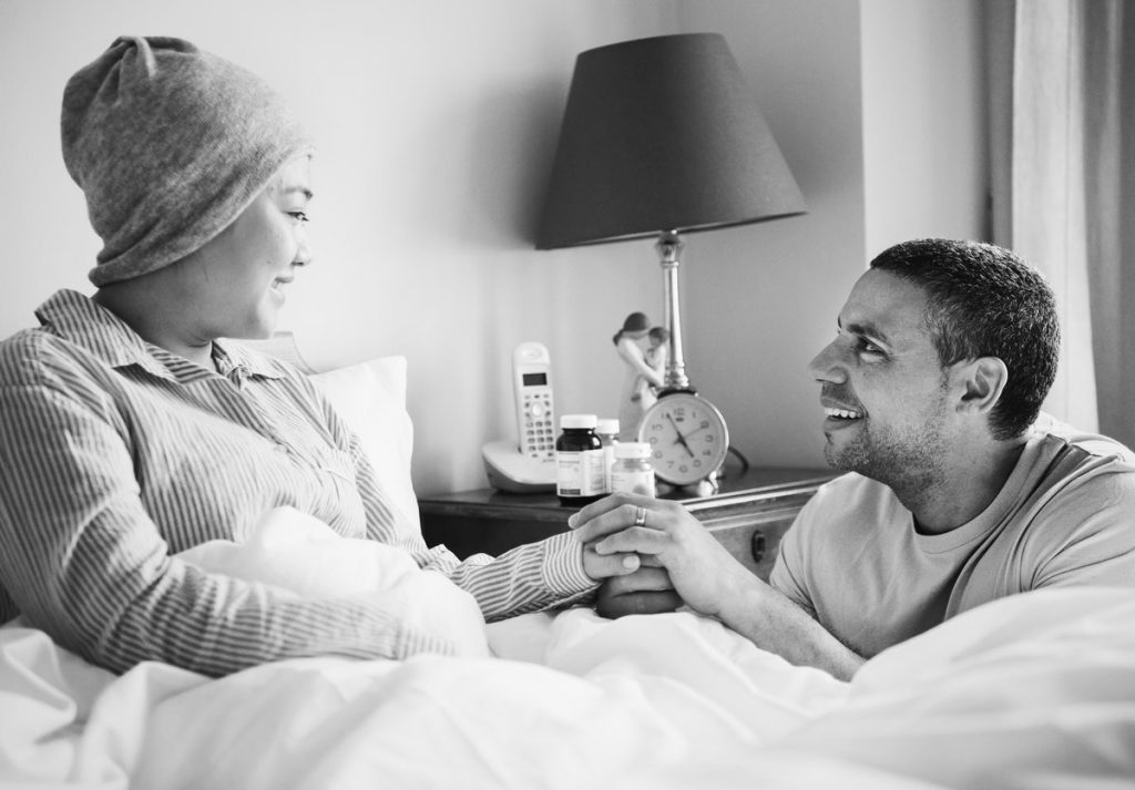 sick woman in bed with partner